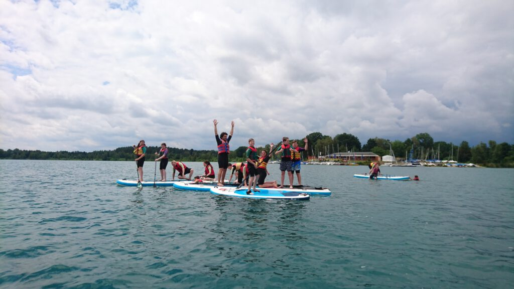 Kids und Betreuer am Wasser beim SUP